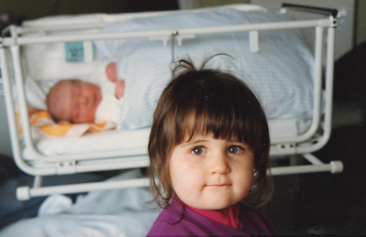 Große Cousine Anna, 2 Jahre, besucht den kleinen Cousin zum ersten Mal im Krankenhaus